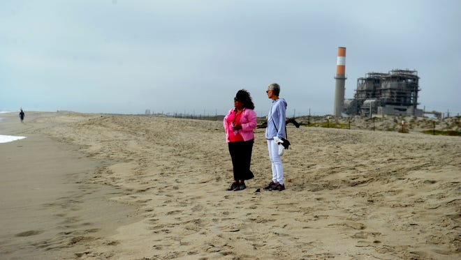 Coco Rasmussen, left, and her friend, Pat O'Hara, walk along the beach near Fifth Street in Oxnard. The Mandalay Generating Station is visible from Mandalay State Beach.