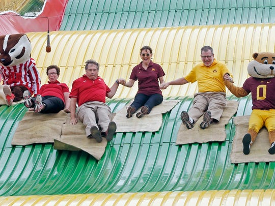 Minnesota and Wisconsin university leaders, spouses and mascots enjoy the giant slide at the Minnesota State Fair Friday, Aug. 26, 2016, in Falcon Heights, Minn.