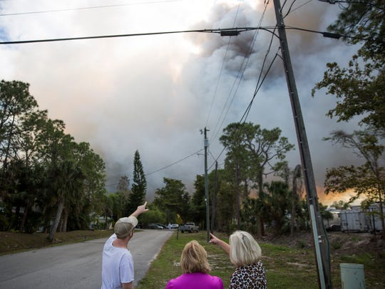 Chuck Toth, left, and Cindy Murlowski, right, point at the smoke from the brush fire as Joanne Pasquea stands with them just south of I-75 and west of Picayune Strand State Forest on Monday, March 6, 2017. Murlowski and Pasquea own Belle Meade ranch near the area of the brush fire where Toth's father, Armond Toth, is the manager. The three discussed how to evacuate the horses from the property as they watched the smoke blow south and west.