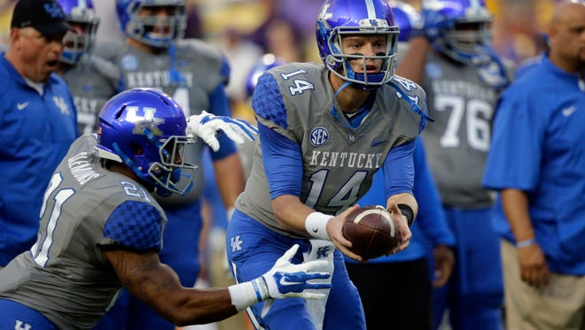 Kentucky quarterback Patrick Towles (14) hands off to running back Josh Clemons (21) during warm ups before an NCAA college football game in Baton Rouge, La., Saturday, Oct. 18, 2014. (AP Photo/Gerald Herbert)
