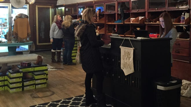 Lori Troutwine, far right, helps a customer in her boutique, Luxe Lizzie's, during Small Business Saturday.
