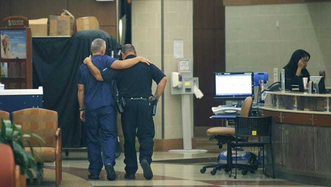 A member of the medical staff and a Rochester Police Officer walk together down the hallway after a press conference confirming that the officer shot on Hudson Avenue died at Rochester General Hospital in Rochester.