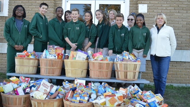 (From left) Destiny Simmons, Connor Triantos, Noah Davis-Logan, Jennifer Duffy, Parker Swift, Angelina Alimenti, Shannon Kavanaugh, Donna Cooper, coordinator, Brayden Brown, Alesia Velez, resource specialist, Naomi Jones, and Ann Mulvihill, family partner, show the items gathered during Edgarton Christian Academy's Student Council Thanksgiving Food Drive, which supported the Monarch Family Success Center of Vineland, which works with families in need to provide a Thanksgiving meal.