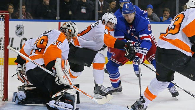 Flyers goalie Ray Emery, left, makes a save on a shot by Rangers left wing Rick Nash on Sunday. Emery will be in goal again for Tuesday night's Game 3.