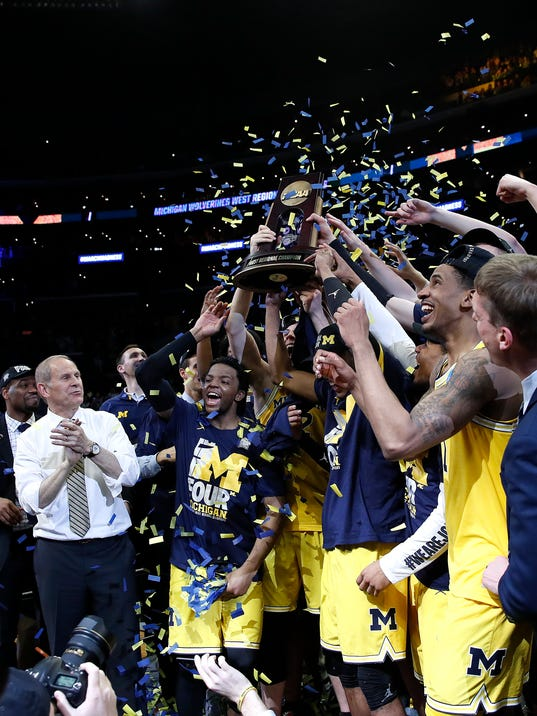 Michigan players celebrate after defeating Florida State 58-54 in an NCAA men's college basketball tournament regional final Saturday, March 24, 2018, in Los Angeles. (AP Photo/Jae Hong)