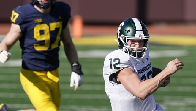 Michigan State quarterback Rocky Lombardi (12) scrambles during the second half of an NCAA college football game against Michigan, Saturday, Oct. 31, 2020, in Ann Arbor, Mich.