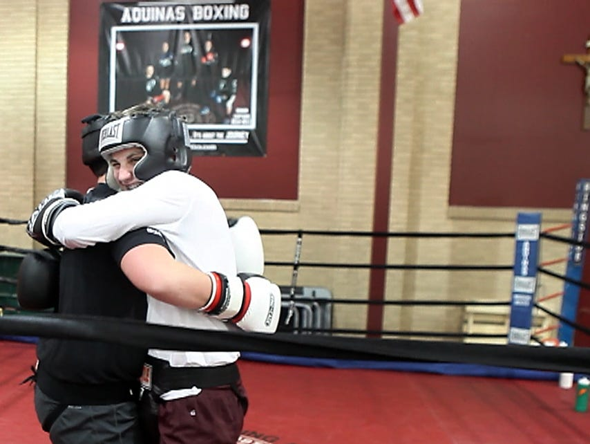 Mike Robertson hugs his sparing partner Michael Bohme after the two went three rounds at boxing practice.