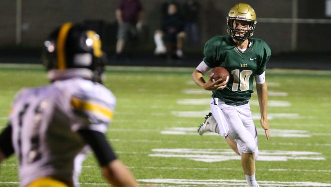 August 26, 2016; Iowa City, IA, USA;  Iowa City West Trojans QB Evan Flitz runs for a first down against the Southeast Polk Rams.  The Trojans beat the Rams 42 to 17.  Mandatory Credit: Reese Strickland-For the Herald