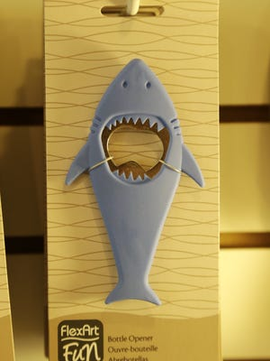 A bottle opener in the likeness of a shark hangs from a hook in a souvenir shop in Chatham, Mass. With growing sightings of great white sharks off Cape Cod, local entrepreneurs are feeding the frenzy with their shark-themed memorabilia and apparel. (AP Photo/Steven Senne)