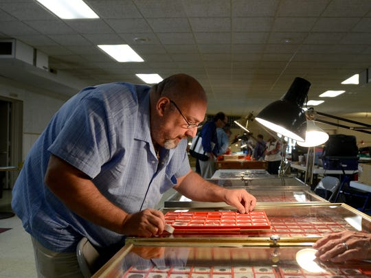 Brian Brown, of Sylvania, Ohio, looks over some coins Sunday, May 22, during the Marysville Coin Club's spring show at the American Legion in Marysville.