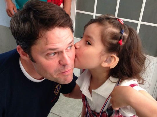Justin Osmond receives a kiss from a girl he helped at the Tepic, Mexico Hearing Mission.