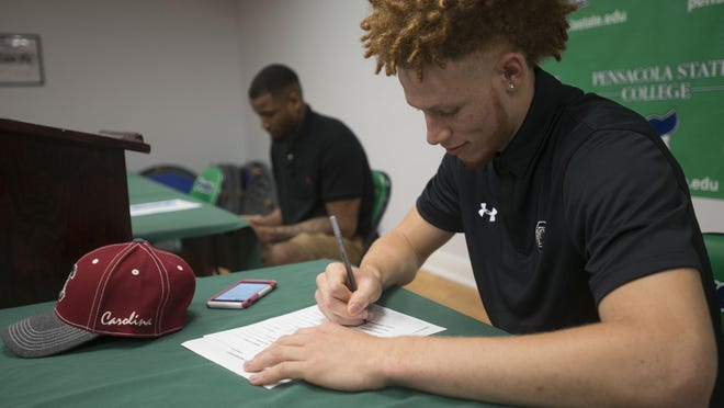 Pensacola State College Basketball players, Hassani Gravett, right, signs a letter of intent with the University of South Carolina while teammate, Johnell Ginnie, signs with the University of North Alabama during a ceremony at PSC Thursday afternoon.