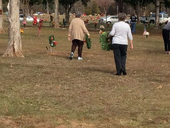 Family members carry wreaths to the gravesites of veterans