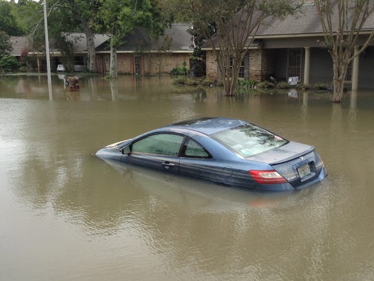 Flooded cars and homes line the street in Lafayette
