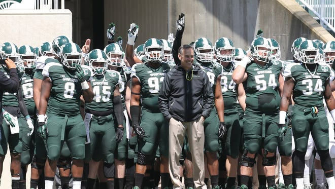 Michigan State coach Mark Dantonio leads his team onto the field for last year's Green and White game on April 26, 2014 at Spartan Stadium.