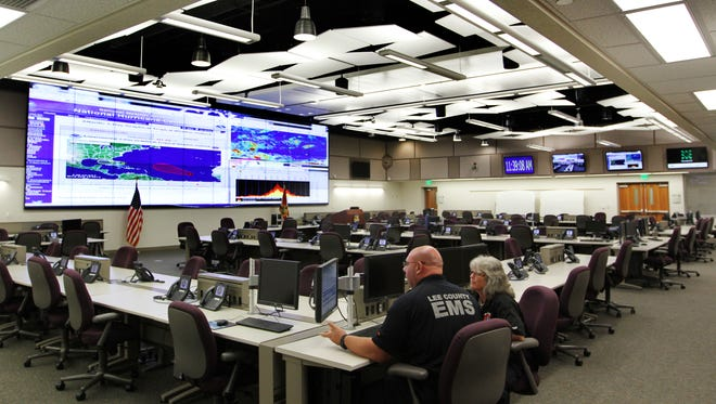 Vinnie Casale and Traci Acton, of Lee County EMS, prepare for training in the situation room at the Lee County Emergency Operations Center.