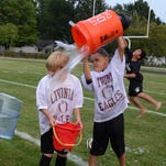 Coach Jenn Brown empties a bucket of cold water on Kaitlyn Brown and Kaitlyn Mitchell.