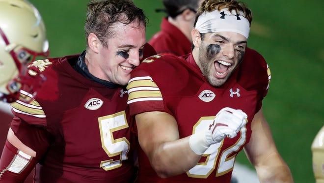 Boston College quarterback Phil Jurkovec (5) and linebacker Nick DeNucci (32) celebrate after the team's Saturday night win over Texas State.