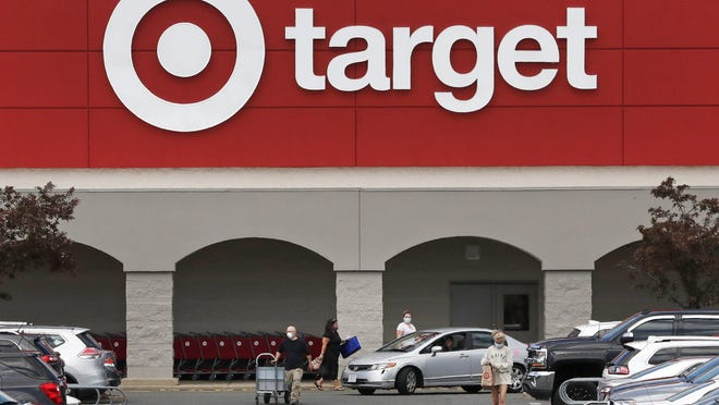 File - Customers, wearing protective masks due to the COVID-19 virus outbreak, head for their cars after shopping at the Target store in Danvers, Mass., Friday, May 15, 2020.