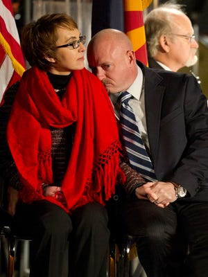U.S. Congresswoman Gabrielle Giffords  and her husband, retired Navy Capt. Mark Kelly, attend  a 2012 vigil at University of Arizona in Tucson marking the one year anniversary of the shootings in which six people were killed.