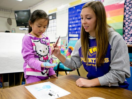 University of Wisconsin - Stevens Point freshman outfielder Kylie Johnson, right, paints second-grader Aryanna Chang's hand to make a snowflake in Anne Leton's classroom at McDill Elementary School in Stevens Point, Friday, Dec. 4, 2015. The UWSP softball team was helping second and third grade students make seasonal decorations to be donated to the assisted living residence at Wellington Place at Whiting.