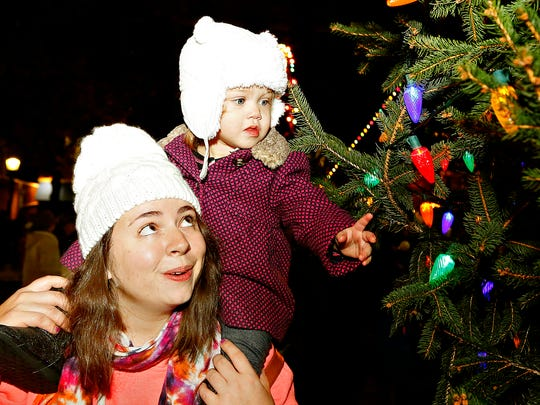 Kelly Caron, left, of Springettsbury Township, holds her daughter 18-month-old Clementine Caron, right, as she looks at the lights on the tree following the York Christmas Tree Lighting Ceremony in downtown York, Pa. on Friday, Dec. 4, 2015. (Dawn J. Sagert - The York Dispatch)