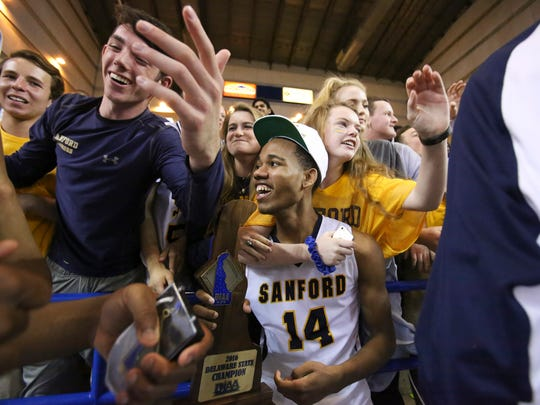 Sanford's Freddie Ryle holds the championship trophy as he joins the Sanford student section after the Warriors' 39-32 win in the DIAA state tournament title game Saturday at the Bob Carpenter Center.