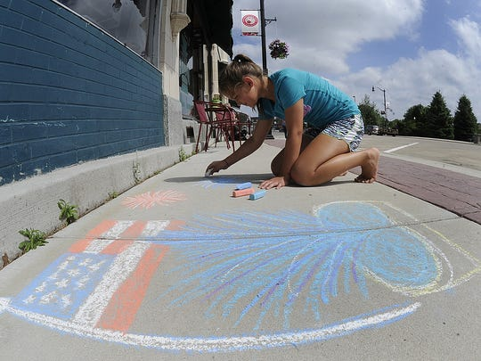 Jasmine Pleet draws artwork on the West Grand Avenue sidewalk during Chalk It Up, 2014