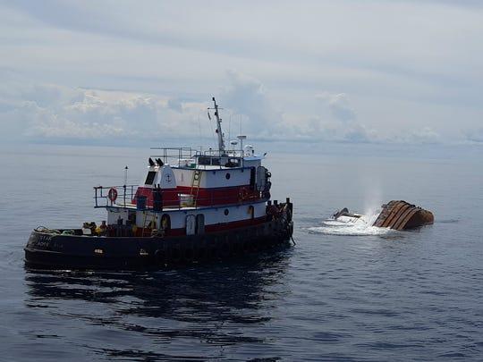 Tug Kathleen begins to slip below the surface of the Atlantic Ocean on Monday, Sept. 26, 2016.