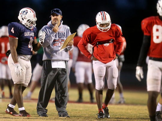 Oakland head football Coach Kevin Creasy works with