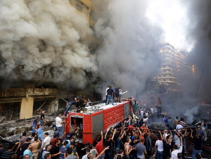 People gather at the scene of a car bomb explosion on Aug. 15 in Beirut. Several people were killed when a powerful car bomb ripped through a neighborhood that is a stronghold of the militant group Hezbollah.