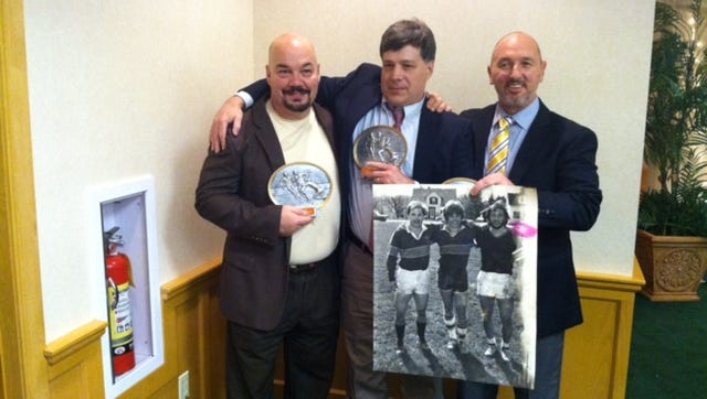Fremont Ross graduate Rick Kusmer, Keith Eedy and Andy Bernoit, left to right, pose with a photo from their playing days at Bowling Green State University. The trio was inducted into BGSU's rugby hall of fame.