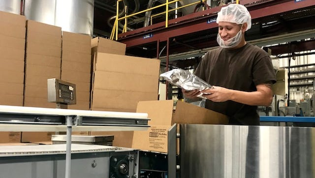 Xavier Escribano packs boxes at the Tim Hortons processing facility in Henrietta.