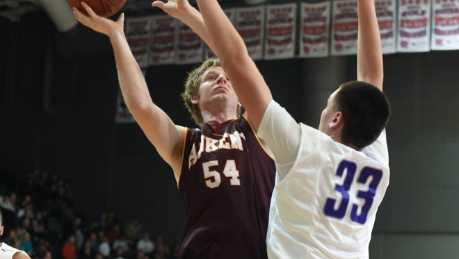 Waukee's Jacob Rau (33) goes up for to block the shot of Ankeny's Joel Roberts (54) at Waukee High School on Friday, Dec. 12, 2014