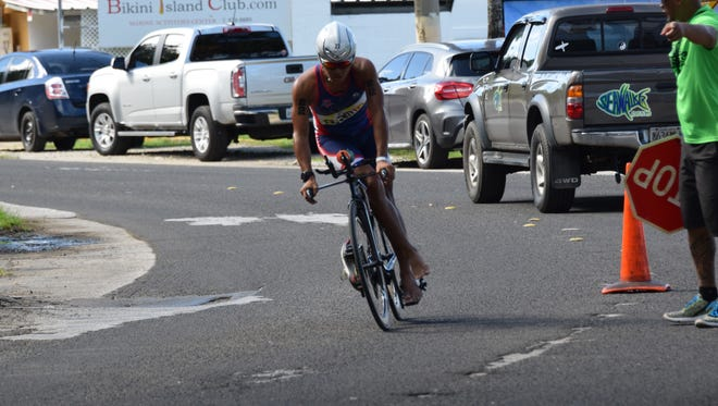 A cyclist rounds a turn and rides to the finish in the bike race portion of the Guam National Triathlon Championships on Sunday, July 23 in Merizo.