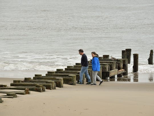 A couple walks over the uncovered storm water outfall