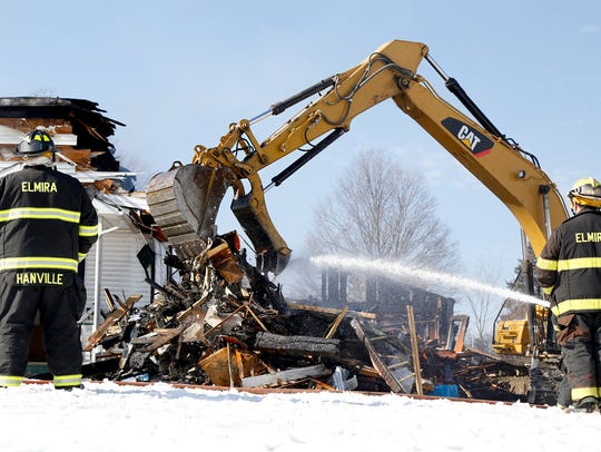 An excavator drops charred debris into a pile at 326
