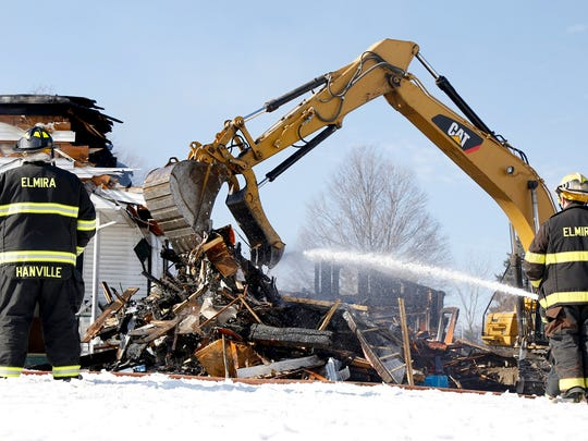 An excavator drops charred debris into a pile at 326 West Ave. on Elmira's Southside Tuesday. A fire ripped through the two-unit home shortly before 5 a.m. The structure is a complete loss.