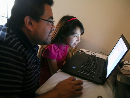 Eduardo Sanchez helps his daughter Citalaly Sanchez, 10, with homework, an online spelling word search, at their far east side home, Indianapolis, Tuesday, May 23, 2017. Eduardo was taken into U.S. Immigration and Customs Enforcement detention for a traffic violation several years ago, and now fears he and his wife Maria Ibrra could be deported.