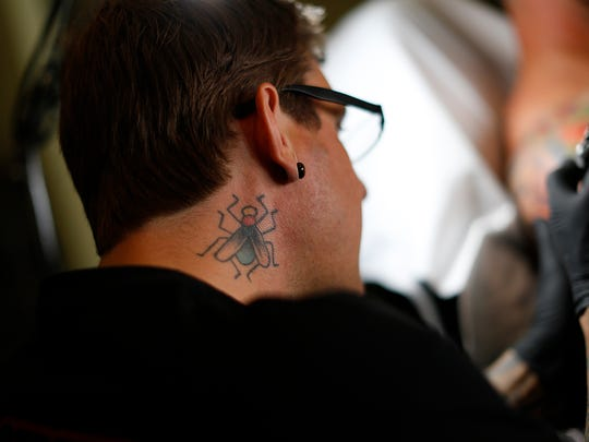 Artist Paul Dhuey works on Ben Chernick at Katana Tattoo in Green Bay on Wednesday, July 30, 2014. Dhuey's tattoo of a fly on his neck was inked to show his dedication to his craft. Evan Siegle/Press-Gazette Media
