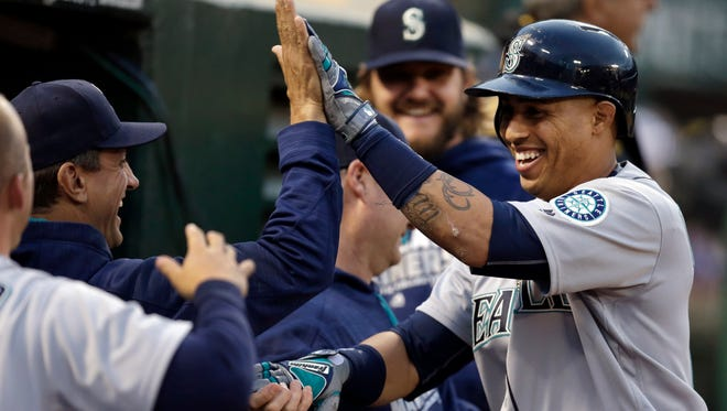 Seattle Mariners' Leonys Martin, right, celebrates after hitting a two run home run off Oakland Athletics' Sonny Gray in the third inning of a baseball game Tuesday, May 3, 2016, in Oakland, Calif.