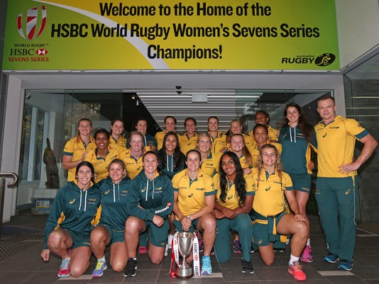 In this June 1, 2016, photo the Australia women's rugby sevens team poses with their world champions trophy in Sydney. The Australian women's team, a mix-and-match ensemble of athletes from other sports, enters the Olympic sevens tournament as world champions, a rare achievement in a series previously ruled by New Zealand. (AP Photo/Rick Rycroft)