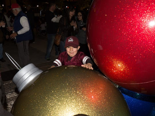 Nathaniel Holguin, 5, plays with the giant tree ornaments during the Christmas Tree Lighting held at the Downtown Plaza on Saturday, Dec. 2, 2017.