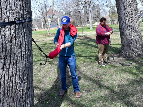 Co-owners Seth Blanchard and Jonathan Steek of Skylark Hammocks work together to take down a hammock they just finished demonstrating during an interview in Gypsy Hill Park on Friday, April 6, 2018.