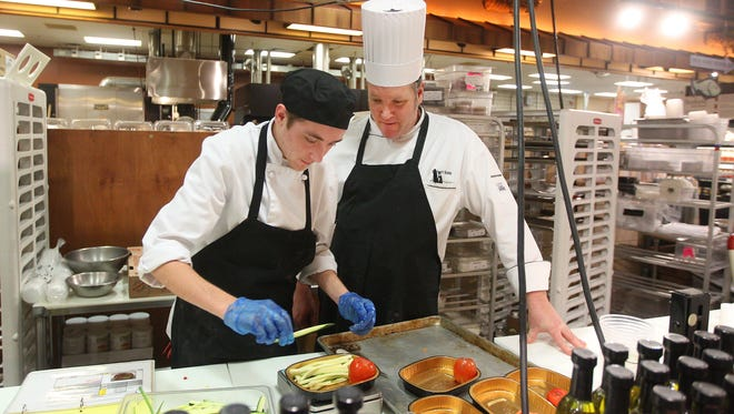 Robert Robb, a sous chef at Wegmans in Pittsford, works with customer service employee Kyle Schuhart in the Ready To Cook Department.