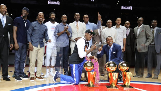 Former Pistons Isiah Thomas and Dennis Rodman pose next to the NBA championship trophies along with teammates during halftime of final game at the Palace of Auburn Hills against the Wizards, April 10, 2017.