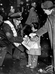 An Old Newsboy accepts a donation from a little girl to help raise money for the Goodfellows fund during the 1953 Christmas season.