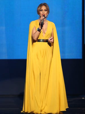 Jennifer Lopez speaks at the American Music Awards in a Michael Costello dress at the Microsoft Theater on Sunday, Nov. 22, 2015, in Los Angeles.
