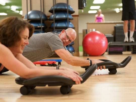 Bobb Prest, right, is a certified personal trainer at Life Time Athletic in St. Louis Park, Minn. He's working client, Carol Greenland.