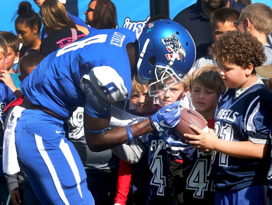 MTSU's Jeremy Cutrer (8) signs a football for a young